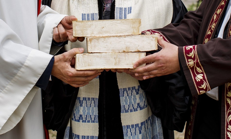 """BERLIN, GERMANY - JUNE 03:  The hands of Rabbi Tovia Ben-Chorin (C), Father Gregor Hohberg (L) and Imam Kadir Sanci (R) are see as they hold symbolic bricks in their hands while standing at the construction site of the future """"House of One"""" at Petriplatz on June 3, 2014 in Berlin, Germany. The initiative aims to bring together Jews, Christians and Muslims in one building that will house a synagogue, a church and a mosque, with a common area for exchange and discussion.  (Photo by Carsten Koall/Getty Images)"""