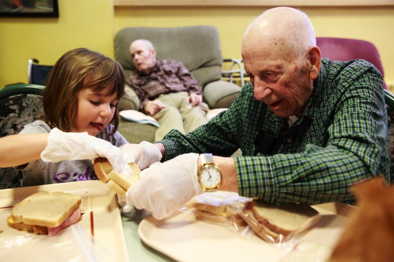 Alex Stafie, 5, and Wallace Scherer, 92, make sack lunches for the homeless during an activity at Providence Mount St. Vincent home for older adults in West Seattle. Children from the Intergenerational Learning Center, a licensed childcare program, is also housed at Providence Mount St. Vincent. Five days a week, the seniors and children connect in a variety of programs including art classes, music time and story time, exercise and one-on-one visiting.